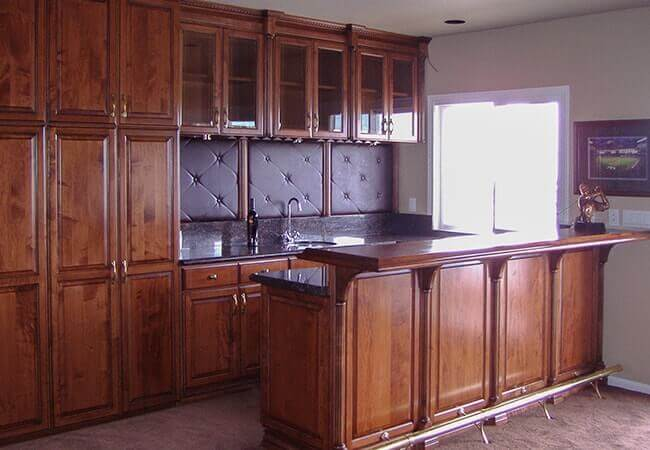 Custom maple bar cabinets with leather backplash